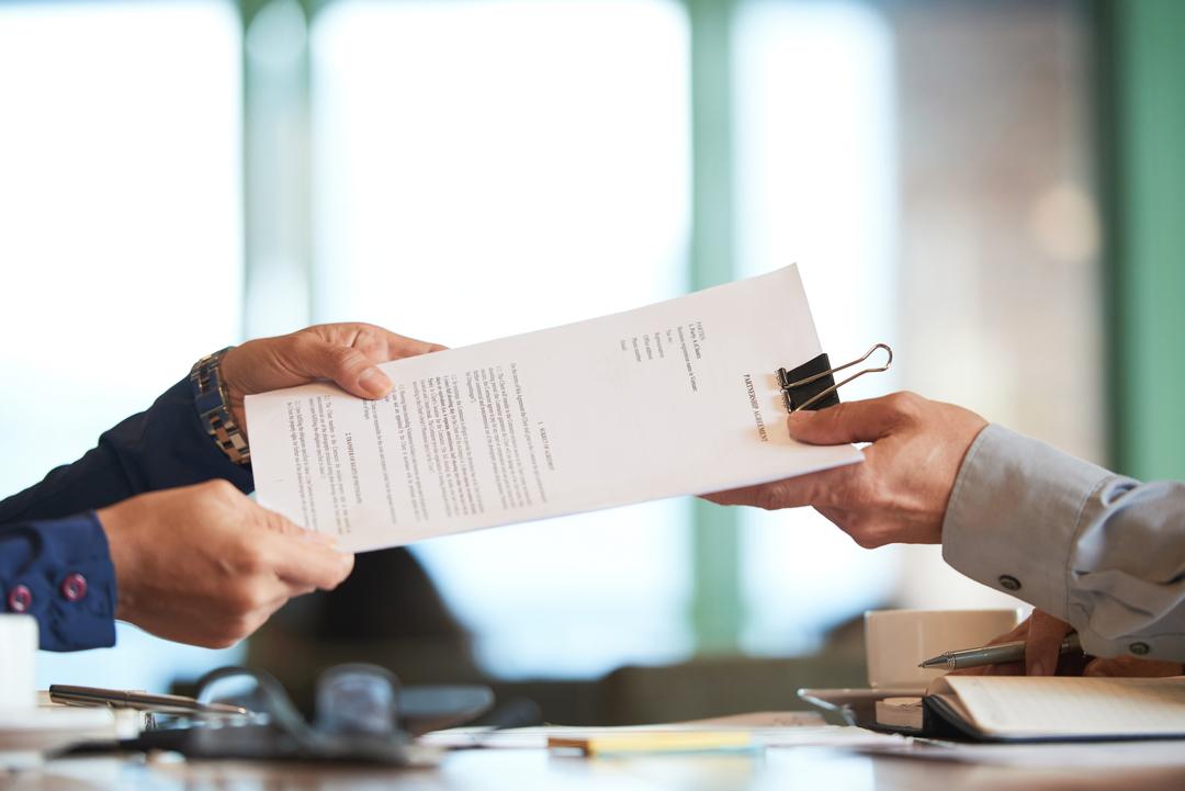 O que é ANTT: homem entrega documento nas mãos de outra pessoa.